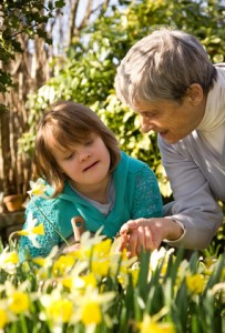 A girl with Down syndrome and her grandmother in a garden.