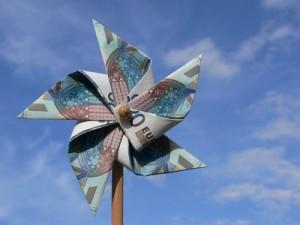 Windrad aus Euroscheinen vor blauem Himmel